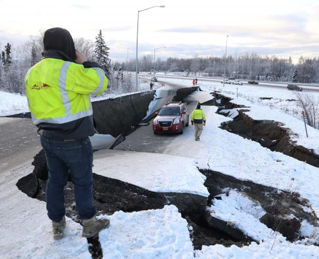 A stranded vehicle lies on a collapsed roadway near the airport in Anchorage. Photo: Reuters