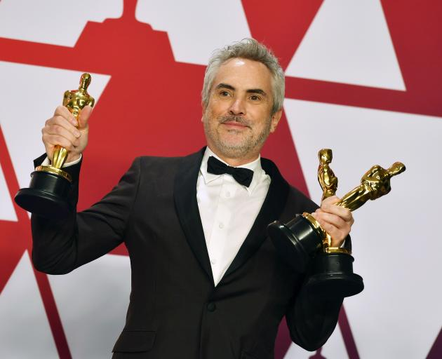 Alfonso Cuaron with Oscars for best director, best foreign language film and best cinematography...