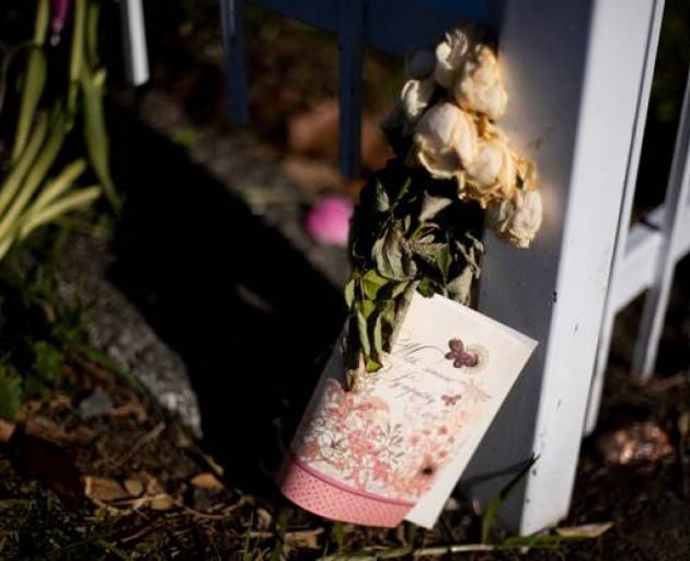Roses left for Angela at the gate outside the entry to her flat, where police were stationed for a week after her death. Photo: Dean Purcell