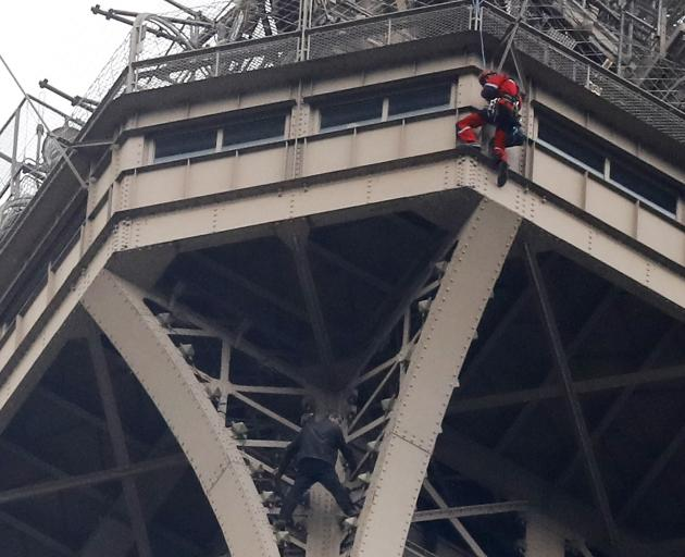 A rescue worker (above in red) descends to the man in black. Photo: AP