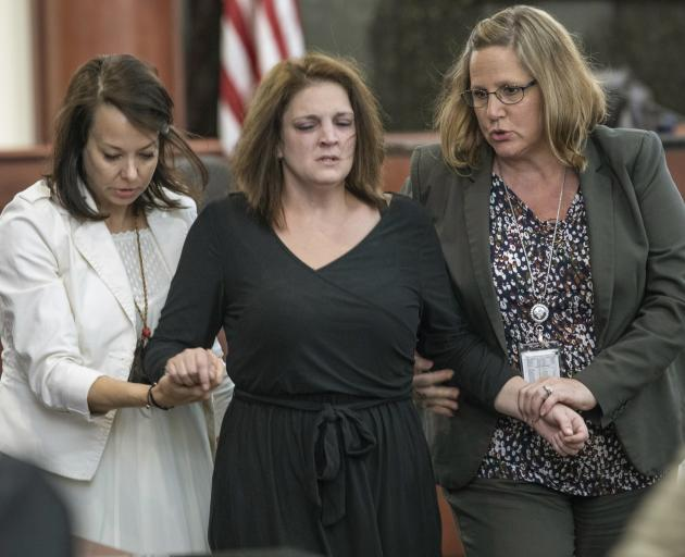 Amber Kyzer (centre) is helped out of the courtroom on Monday. Photo: The State via AP