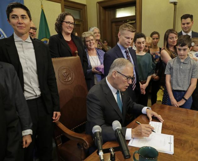 Washington Governor Jay Inslee signs the bill into law on Tuesday. Photo: AP