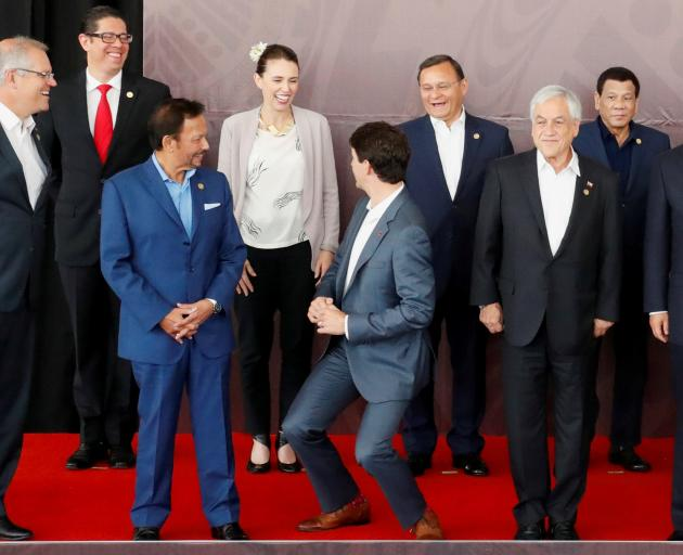 Canada's Prime Minister Justin Trudeau (centre) shares a joke about his height with New Zealand's Prime Minister Jacinda Ardern on Sunday. Photo: Reuters