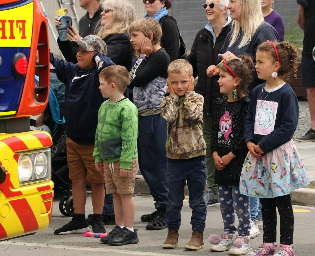 Young spectators cover their ears as the fire sirens on the vintage fire engine driven by the...