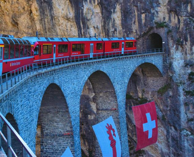 Bernina Express crosses the arched Landwaller viaduct and goes into a mountain.