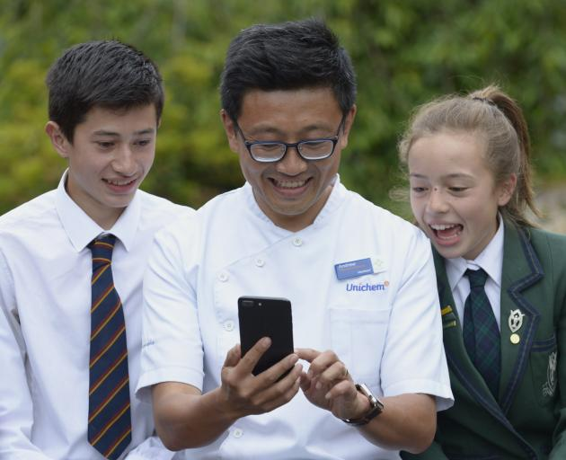 Roslyn Pharmacy owner Andrew Hou, holds a smartphone, watched by son Josh and daughter Ella. PHOTO: GERARD O'BRIEN