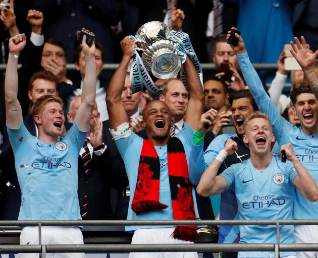 Vincent Kompany lifts the trophy as Manchester City teammates celebrate.  Photo: Action Images...