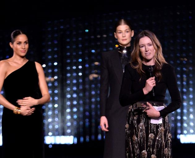 Clare Waight Keller accepts her award with Meghan (left) and actress Rosamund Pike. Photo: Getty...