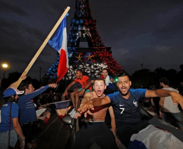 Blue, White, and Red lights and two World Cup stars are projected on the Eiffel Tower after France win the Soccer World Cup final. Photo: Reuters