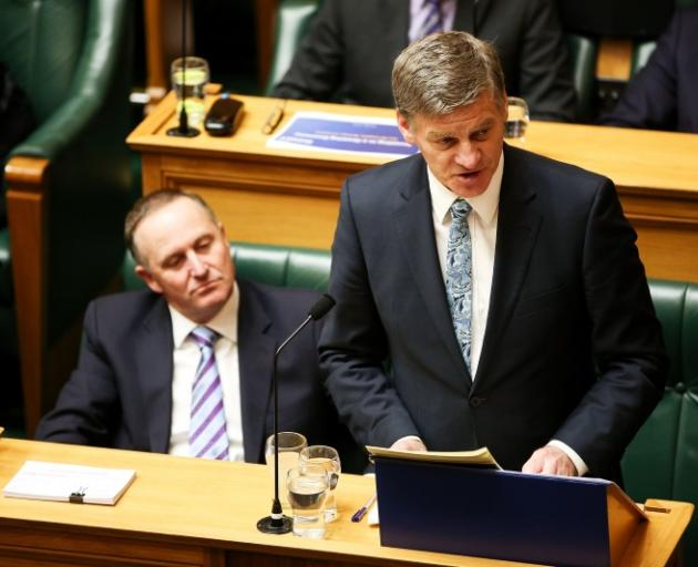 Finance Minister reads the Budget and Prime Minister John Key looks on at Parliament this afternoon. Photo by Getty