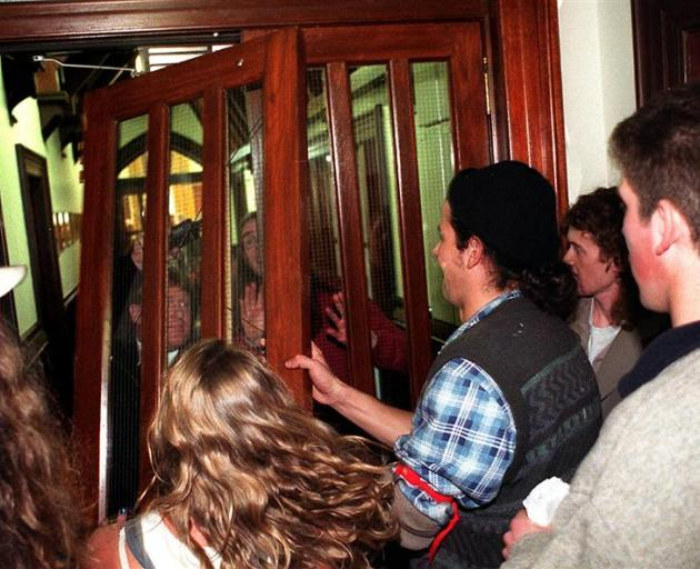 Protestors break down a door in the University of Otago Registry as they disrupt a University Council meeting in September 1997. The meeting was discussing cuts to the University's European languages and Classics departments.