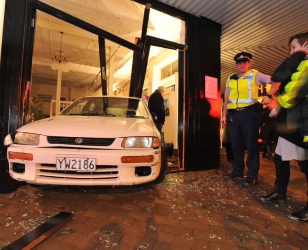 Gallery De Novo owner Richelle Byers looks at the car that crashed through the door of her art gallery last night. Photo by Gregor Richardson.