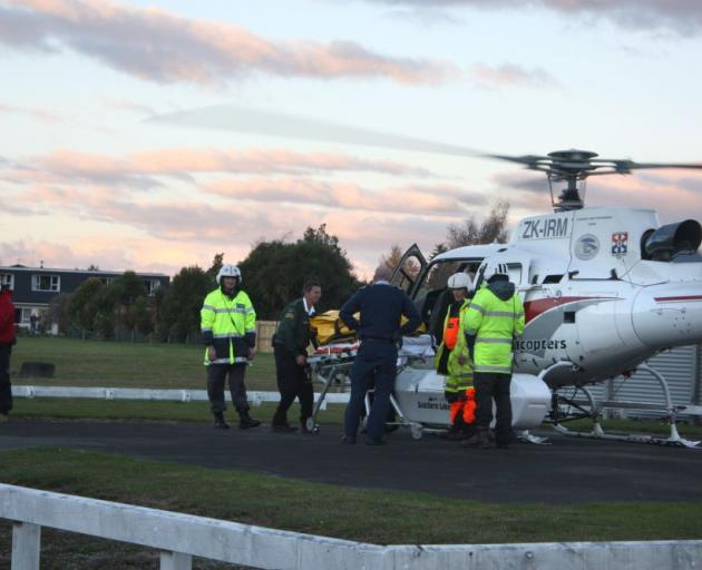 Rescuers remove the body of Yessica Asmin from a helicopter in Te Anau yesterday after she died crossing a Fiordland river. Photo by Brendan McBryde (Fiordland Advocate)