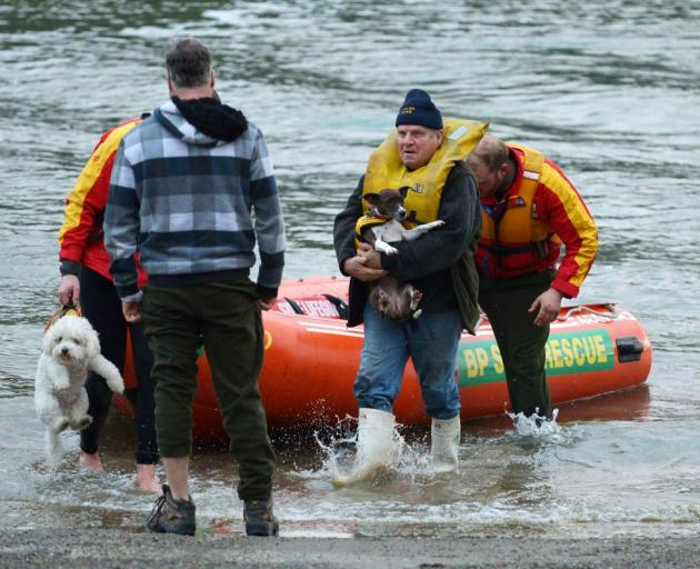 Skipper Alan Eade (centre) comes ashore with dogs Popcorn and Rudi after being rescued by Surf Lifesaving Otago callout squad members near Taieri Island yesterday morning. Photo by Gerard O'Brien