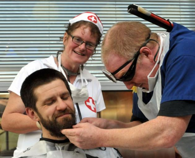 David Steer gets his head shaved yesterday by colleague Simon Fogarty, while Monica Barkman watches proceedings. Photo by Gregor Richardson