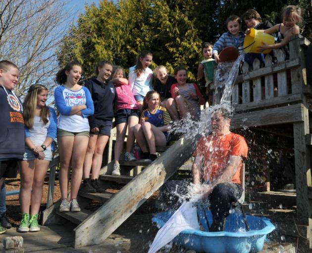 Outram School principal Jeremy Marshall gets icy water poured over him yesterday to fundraise for CanTeen. Photo by Gregor Richardson.