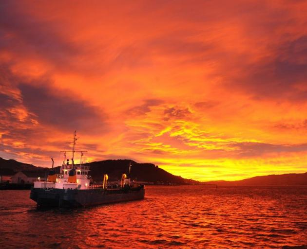 The dredge New Era sails into a red dawn on Otago Harbour. Photo: Stephen Jaquiery