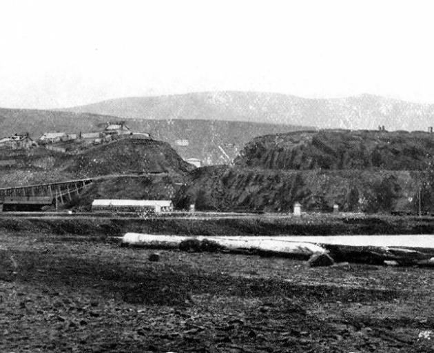 Bell Hill, a prominent landmark was demolished in the 1860s and '70s and the spoil used to reclaim the mudflats in the harbour. This photograph was taken in 1865 from the Triangle (now Queens Gardens). Photo from Otago Witness.