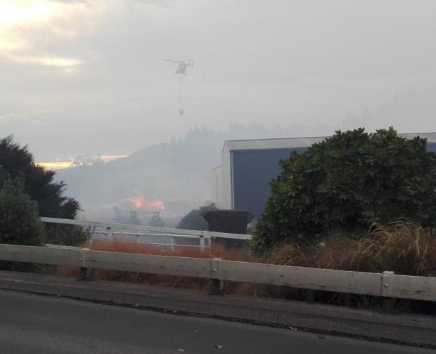 Helicopters battle a blaze in a large woodpile next to ABS Sandblasting on Kaikorai Valley Rd...