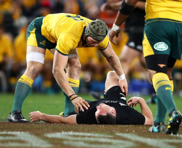 Wallaby David Pocock checks on Ryan Crotty after he was knocked down early in the match. Photo:...