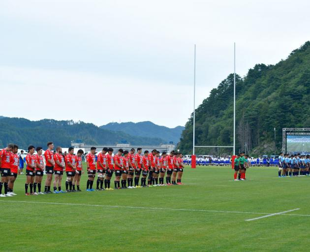 Players observe a minute of silence for the victims of the Great East Japan Earthquake and...
