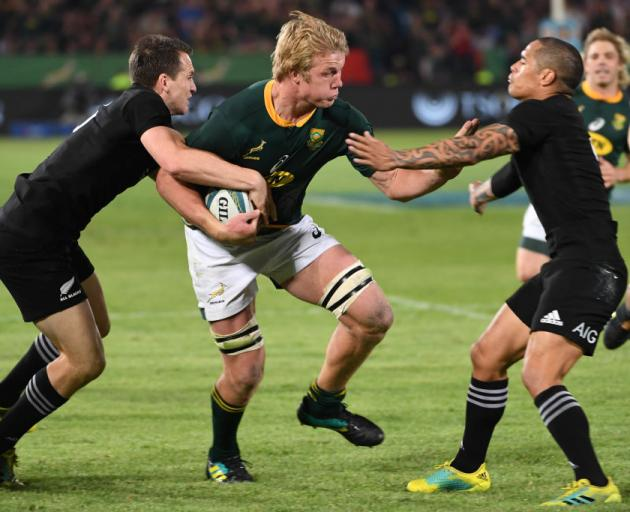 Ben Smith (left) and Aaron Smith try to stop a barnstorming Springbok Pieter-Steph du Toit in...