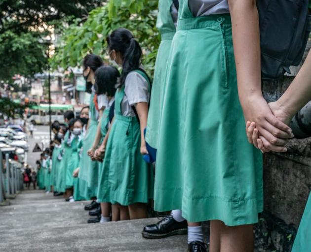 Children join hands to form part of a human chain after weeks of violence in Hong Kong. Photo:...