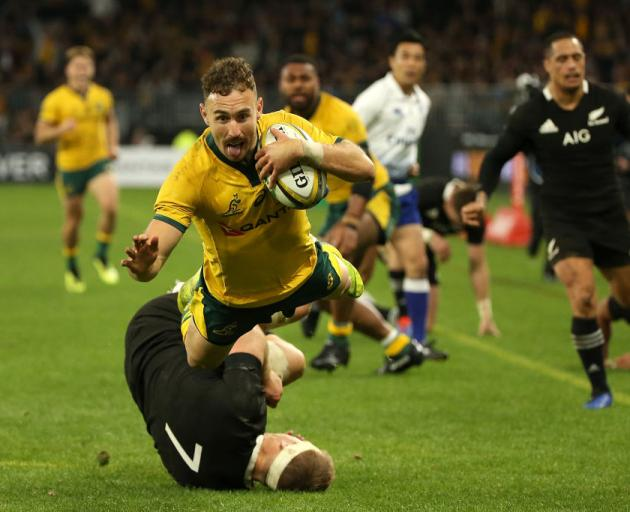 Nic White dives in for a try over Sam Cane. Photo: Getty Images