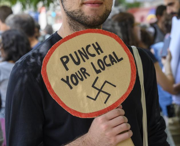 A protestor in Portugal holds a sign opposing far right groups. Photo: Getty Images