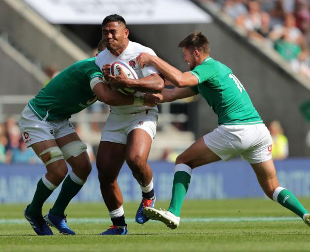 English midfield back Manu Tuilagi is tackled by Josh van der Flier (left) and Ross Byrne, of...