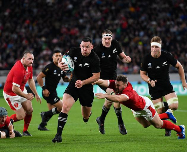All Black Ryan Crotty evades the tackle of Wales' Owen Lane to score a try during the bronze...