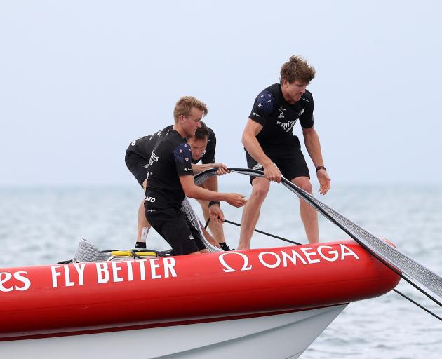 Team New Zealand skipper Peter Burling (right) helps retrieve a sail from the stricken American...