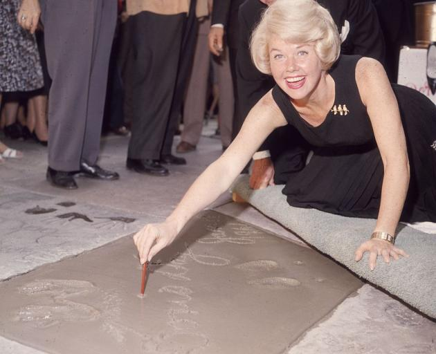 Doris Day signs her name in cement on the Hollywood Walk of Fame in 1961. Photo: Getty Images