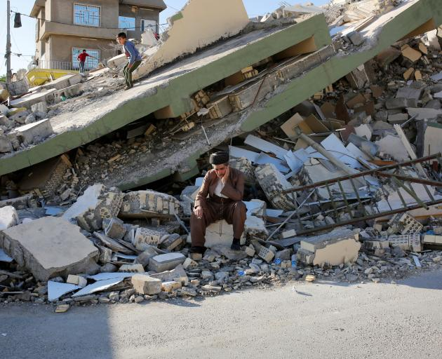 A man sits on a concrete in front the collapsed building at Derbendihan district of Sulaymaniyah in Iraq. Photo: Getty Images