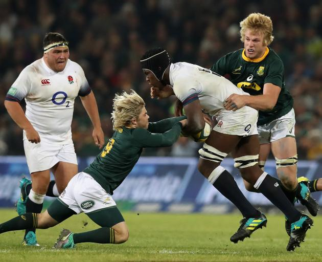 Maro Itoje of England is tackled by Faf de Klerk (left) and Pieter-Steph du Toit. Photo: Getty...