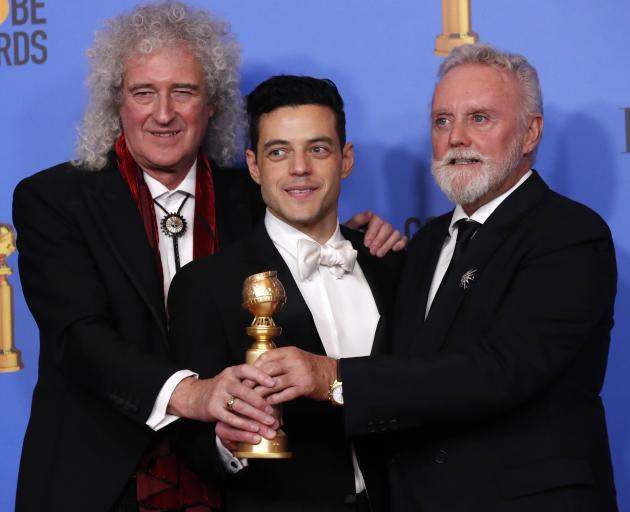 Bohemian Rhapsody's Rami Malek (centre) celebrates with Queen's Brian May (left) and Roger Taylor...