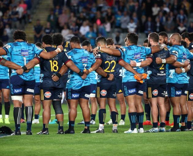 Highlanders and Blues players linked arms to honour the Christchurch mosque victims before the...