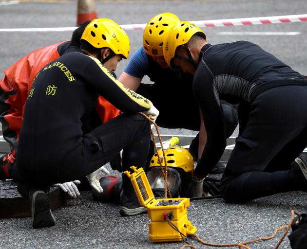 A rescue diver from the Fire Service department enters the sewage system to search anti...
