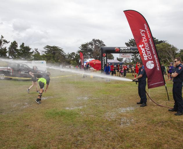 Firefighters from Anzac station welcome competitors to the finish line. Photo: Geoff Sloan