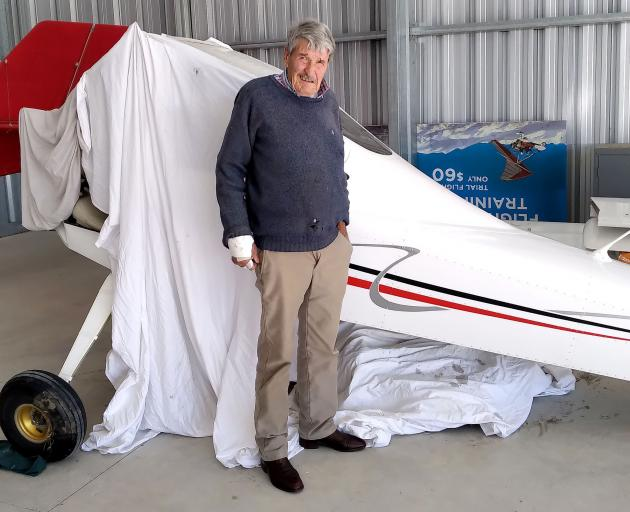 Alan Macdonald with the wrecked aircraft. Photo: Geoff Sloan