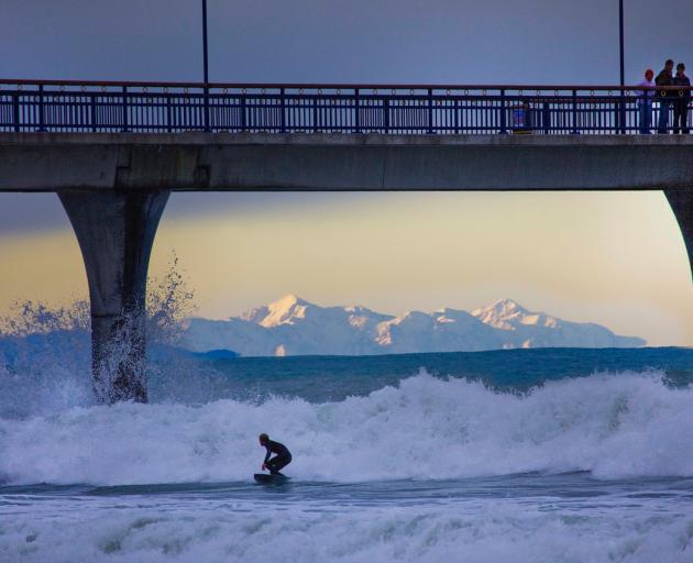 McCombe snapped this photo of a surfer under New Brighton pier. Photo: John McCombe