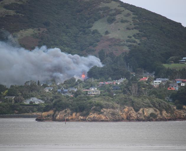 Smoke and flames can be seen pouring from the Beaconsfield Rd house from Port Chalmers. Photo:...