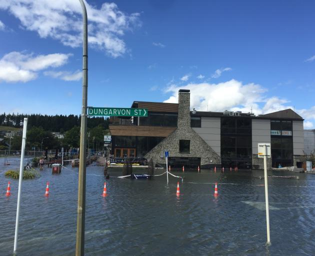 Water laps close to businesses on the waterfront in Wanaka late on Saturday afternoon. Photo:...