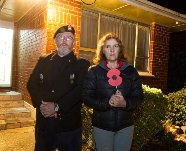 John Cosgrove stands with his wife Kathleen in front of their house to commemorate Anzac Day....