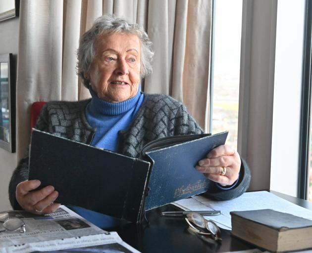 Joyce Raffills (88) looks through one of her photo albums, which contains skiing photos, at...