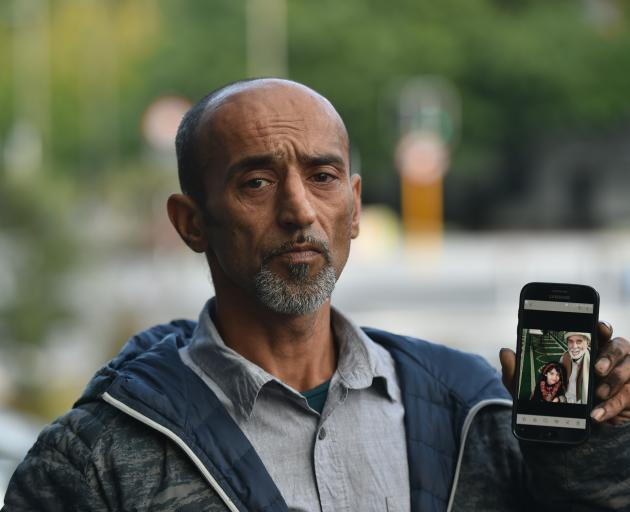 Omar Nabi holds a photo of his father, killed yesterday at the Deans Ave mosque. Photo: Gregor...