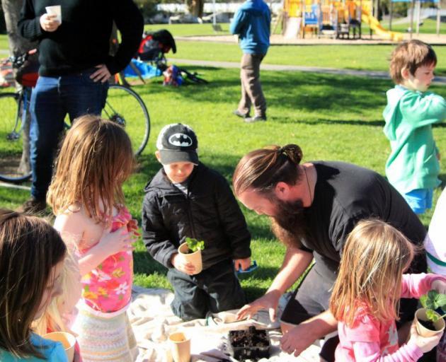 Christchurch community gardener Michael Reynolds helps children pot strawberries.PHOTO: SUPPLIED