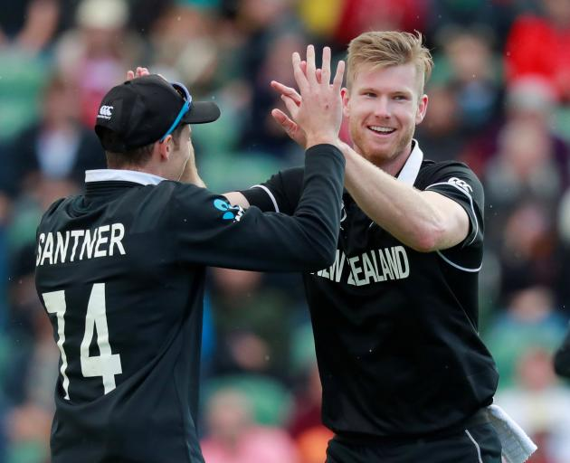 Jimmy Neesham (right) celebrates the wicket of Afghanistan's Najibullah Zadran with Mitchell...