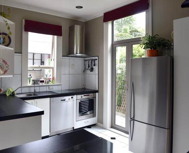White and reflective surfaces make the small kitchen look bigger. The French doors replaced an...