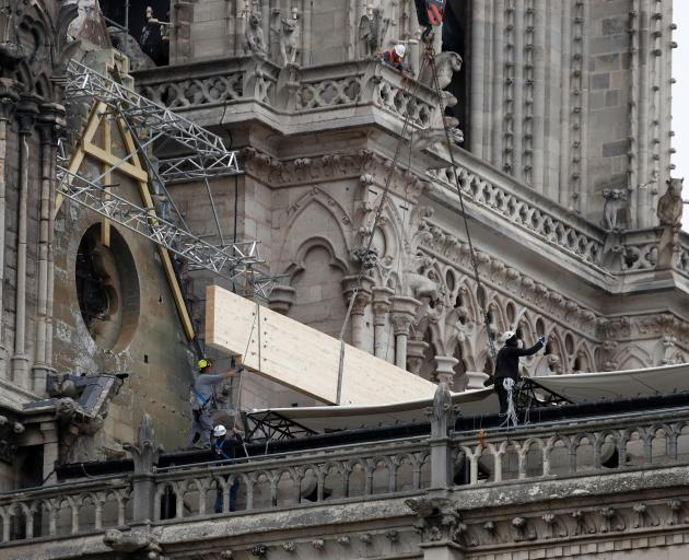 Workers install temporary tarpaulins to protect a fragile Notre-Dame Cathedral. Photo: Reuters